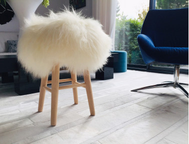 "Wooden stool ""Lina"" sitting white Icelandic sheepskins"