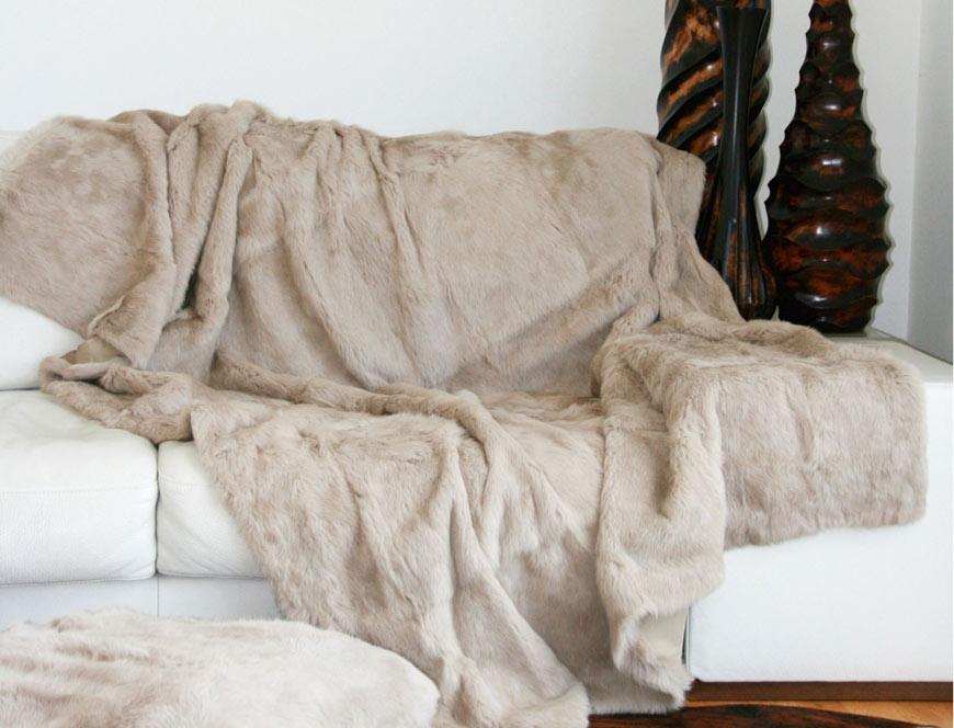 Plaid en fourrure de lapin beige sur un canapé blanc