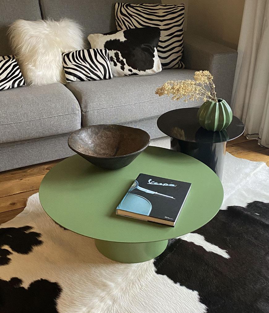 Peau de vache noire et blanche et coussins sur le canapé