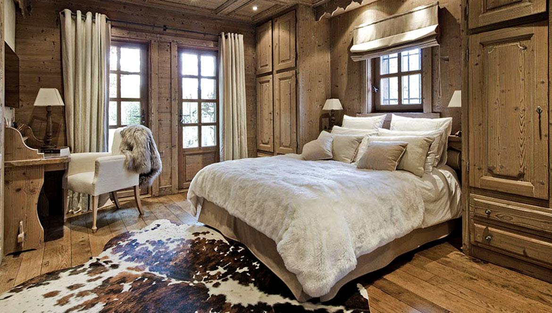 Chambre chalet avec peau de vache normande claire au sol et plaid en peau de mouton blanche rasée sur le lit